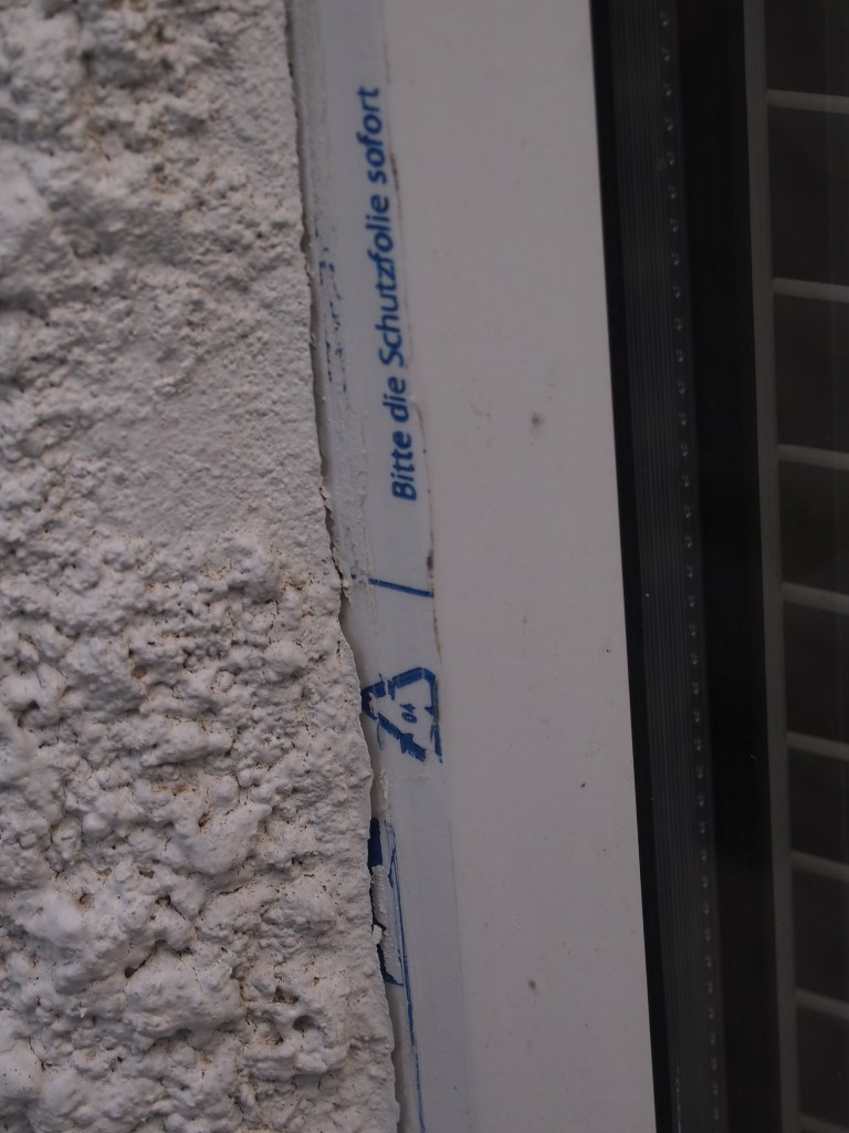 Protective film not removed from windows and unsealed junction with render. A direct pathway for rainwater ingress.