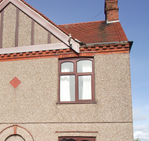 Cracked render caused by underlying structural movement. Note spreading roof tiles near roof verge.