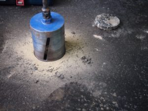 Bitumin oversite removed and coring through concrete slab for sampling.
